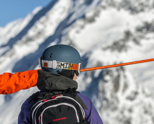 SKI INSTRUCTOR POINTING AT MOUNTAIN WITH CLIENT